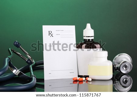 Pharmacist prescription with drops and pills isolated on green - stock photo
