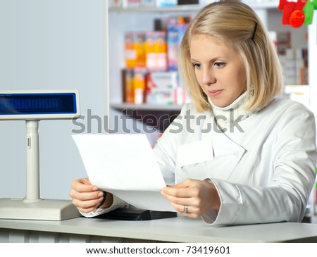 Pharmacist reading prescription at pharmacy. - stock photo