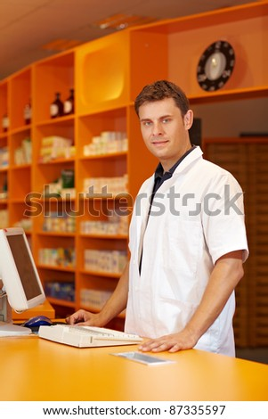 Pharmacist serving behind the counter of a pharmacy - stock photo