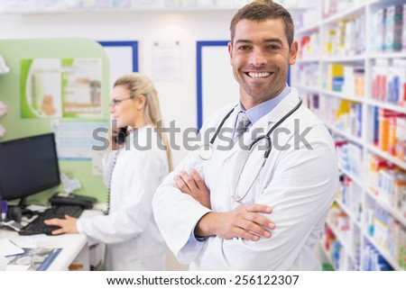 Pharmacist smiling with pharmacist behind on the phone at the hospital pharmacy - stock photo