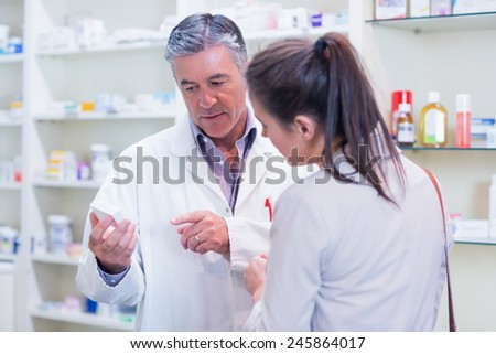 Pharmacist speaking with cheerful young customer in the pharmacy - stock photo