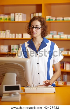 Pharmacist typing on computer behind pharmacy counter - stock photo