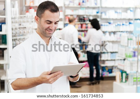 Pharmacist using a tablet to Placing Orders. In the background we can see two customers at the pharmacy - stock photo