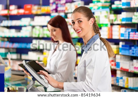 Pharmacist with female assistant in pharmacy standing at the cash point - stock photo