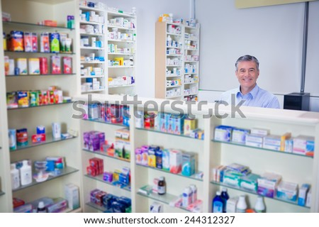 Pharmacist with grey hair standing behind shelves of drugs in the pharmacy - stock photo