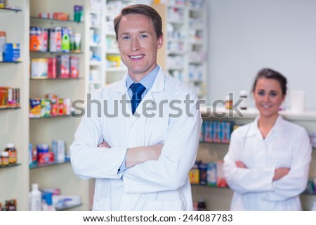 Pharmacist with his trainee standing with arms crossed in the pharmacy - stock photo