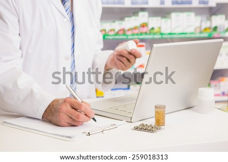 Pharmacist writing on clipboard and holding medication in the pharmacy - stock photo