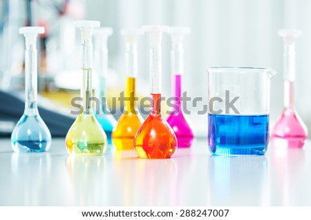 Pharmacy and chemistry theme. Test glass flask with solution in research laboratory. Shallow DOF. Focus on red bottle. - stock photo