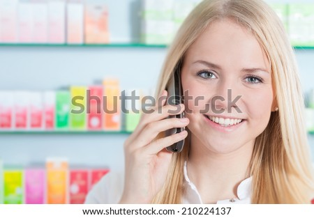 Pharmacy assistant making a phone call - stock photo