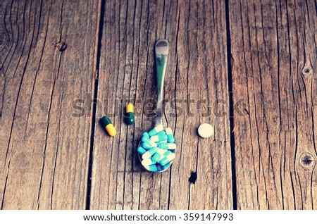 Pharmacy background. Full spoon of pills on a wooden table. Medicine. Natural background. Capsule on a spoon. Close up  - stock photo