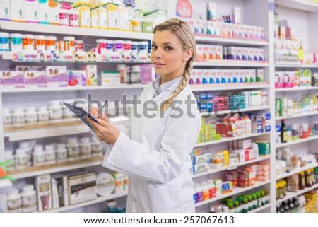 Pharmacy intern writing on clipboard in the pharmacy - stock photo