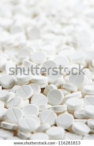Pharmacy theme, Heap of white round medicine tablet antibiotic pills. Shallow DOF - stock photo