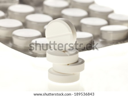 Pharmacy theme. Heap of white round medicine tablet pills and blister. - stock photo