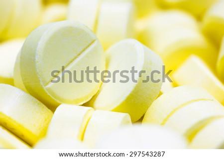 Pharmacy theme, Heap of yellow round medicine tablet antibiotic pills. Shallow DOF - stock photo