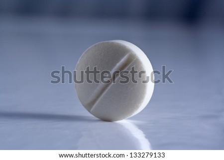 Pharmacy theme, white medicine tablet antibiotic pill. Shallow DOF. Color balance is in blue for more drama - stock photo