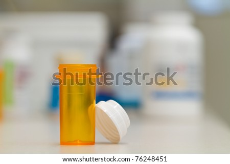 pharmacy vial, empty, in a pharmacy, stock bottles in the background - stock photo