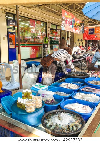 PHAYAO, THAILAND - JUNE 13 : Unidentified market woman prepare her goods for sell on June 13,2013 at Kadhoykam market Phayao, Thailand. Her seafood stall is notable in the market. - stock photo