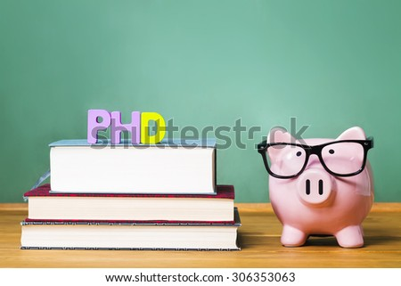 PhD degree theme with textbooks and piggy bank with glasses on green chalkboard background - stock photo