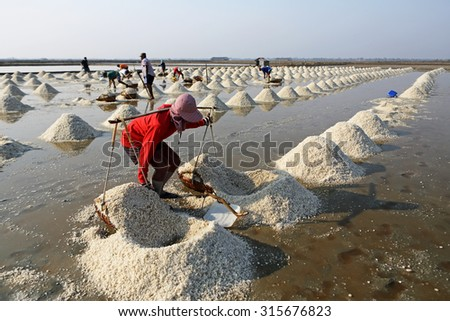 PHETCHABURI, THAILAND - MAR 28: Unidentified workers carrying salt at the salt farm on March 28, 2013 in Phetchaburi,Thailand. It is a salt production is one of a great wide industry of  Phetchaburi - stock photo