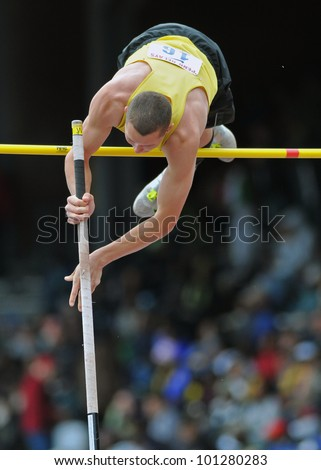 PHILADELPHIA - APRIL 28: A pole vaulter in the boys high school pole vault championship clears the bar at the 2012 Penn Relays April 28, 2012 in Philadelphia. - stock photo