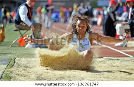 PHILADELPHIA - APRIL 25: Jasmine Kent from Georgia Tech lands in the sand in the ladies college long jump competition  during the 2013 Penn Relays April 25, 2013 in Philadelphia. - stock photo
