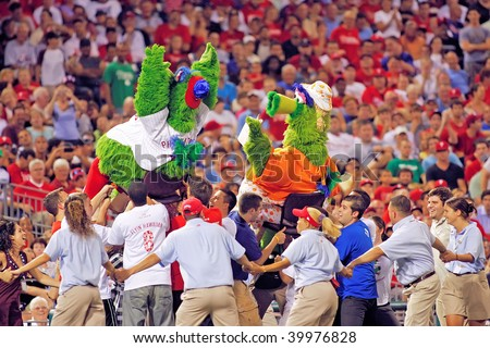 PHILADELPHIA - AUGUST 20: Phillie's mascot the Phanatic and Mrs. Phanatic are hoisted in the air by Phillie's fans during the game between the Diamondbacks and the Phillie's on August 20, 2009 - stock photo