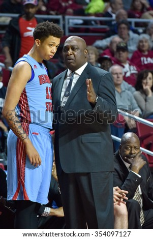 PHILADELPHIA - DECEMBER 19: Delaware State Hornets head coach Keith Walker talks to one of his players on the sideline during the basketball game December 19, 2015 in Philadelphia.  - stock photo
