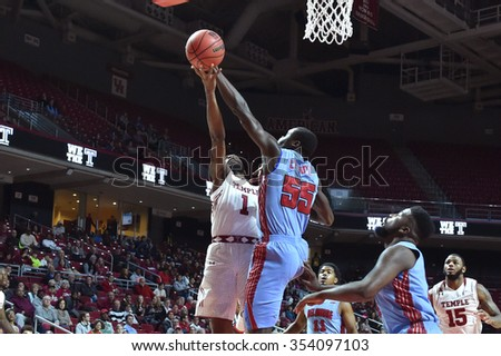 PHILADELPHIA - DECEMBER 19: Temple Owls guard Josh Brown (1) has his shot blocked by Delaware State Hornets center Demola Onifade (55) during the basketball game December 19, 2015 in Philadelphia.  - stock photo