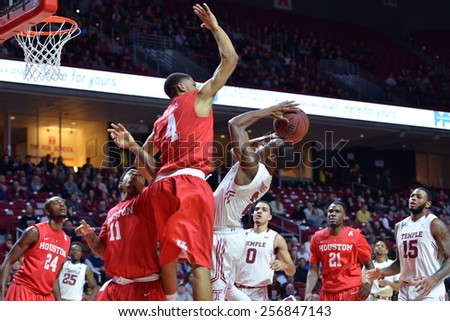 PHILADELPHIA - FEBRUARY 26:  Houston guard LeRon Barnes (4) leaps over Temple Owls guard Will Cummings (2) for a blocked shot during the AAC college basketball game  February 26, 2015 in Philadelphia. - stock photo