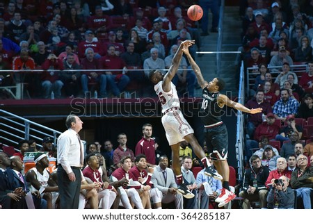 PHILADELPHIA - JANUARY 16: Temple Owls guard Quenton DeCosey (25) fires up a long shot as his coach watches during the American Athletic Conference basketball game January 16, 2016 in Philadelphia.  - stock photo