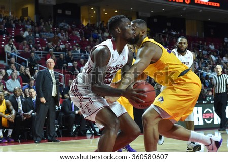 PHILADELPHIA - JANUARY 9: Temple Owls guard Quenton DeCosey (25) is fouled hard going up for a shot during the American Athletic Conference  basketball game January 9, 2016 in Philadelphia.  - stock photo
