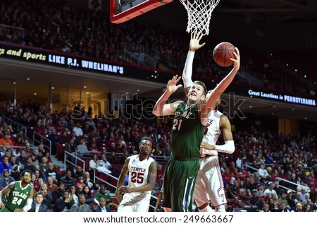 PHILADELPHIA - JANUARY 31: Tulane Green Wave center Dylan Osetkowski (21) shoots over a Temple defender during the AAC conference college basketball game January 31, 2015 in Philadelphia.  - stock photo