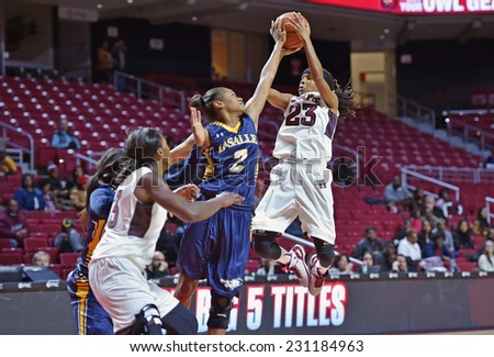 PHILADELPHIA - NOVEMBER 14: Temple Owls guard Tyonna Williams (23) tries to shoot over a defender during the season opening ladies basketball game against LaSalle November 14, 2014 in Philadelphia.  - stock photo