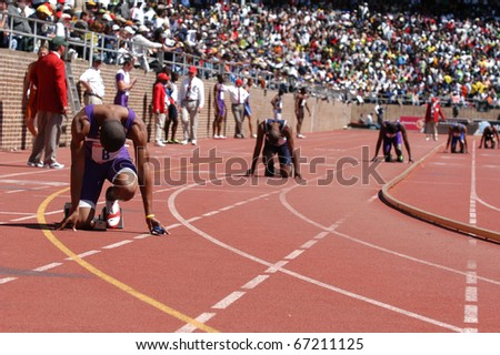 PHILADELPHIA, PA - APRIL 29: Unidentified college men runners ready to start relay race on Saturday, April 29, 2006 in Philadelphia. This is the 112th Penn Relays at the University of Pennsylvania's Franklin Field - stock photo