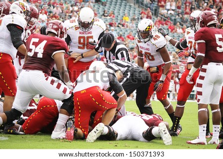 PHILADELPHIA, PA. - SEPTEMBER 8: Maryland and Temple players battle for the football after a fumble during a game on September 8, 2012 at Lincoln Financial Field in Philadelphia, PA.  - stock photo