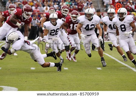 PHILADELPHIA, PA. - SEPTEMBER 17: Penn State defenders led by #2 Chaz Powell close in on Temple's Bernard Pierce on September 17, 2011 at Lincoln Financial Field in Philadelphia, PA. - stock photo