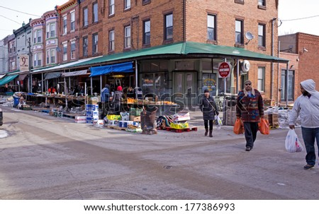 PHILADELPHIA, PA, USA-FEBRUARY 16, 2014:  Shoppers hurrying home on a cold winters morning from Philadelphia's Italian market. The market is the oldest working outdoor market in the United States. - stock photo