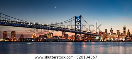 Philadelphia skyline and Benjamin Franklin Bridge at dusk as seen from Camden, New Jersey - stock photo