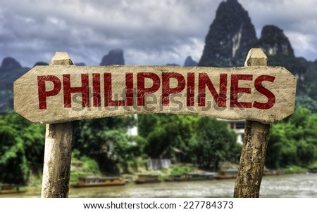Philippines wooden sign with a rural background - stock photo