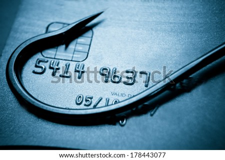 phishing / fish hook on a credit card / computer threats / cyber crime  - stock photo