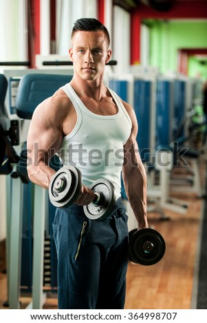 phisique fitness competitor works out in gym lifting dumbbells - stock photo