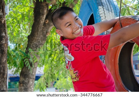PHITSANULOK,THAILAND - NOVEMBER 22, 2015 smiling boy on obstacle course in park,Thailand - stock photo