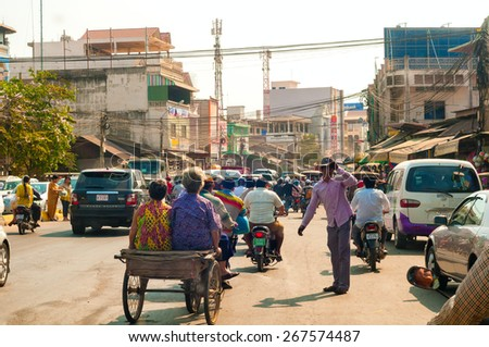 PHNOM PENH, CAMBODIA - FEBRUARY 28, 2014: Congested traffic of all types makes slow progress along National Highway 1 in the southeast section of the Cambodian capital. - stock photo