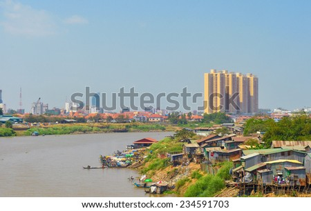 PHNOM PENH, CAMBODIA - MARCH 1, 2014: Shanties and small watercraft along the Bassac River, a distributary of the Mekong,contrast with distant modern high rises in this fast-developing Asian capital. - stock photo