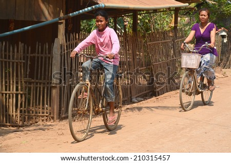PHNOM PHEN, CAMBODIA MARCH 23: Unidentified street child biking on march 23 2013 in Phnom Phen,Cambodia.In Phnom Penh alone there are between 10,000 and 20,000 children live and work on the streets - stock photo