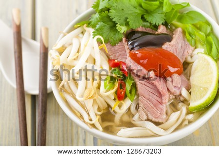 Pho Bo - Vietnamese fresh rice noodle soup with beef, herbs and chili topped with hoisin and chill sauce. Vietnam's national dish. - stock photo