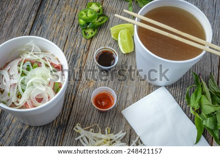 Pho Fast Food To Go on Wood Background with Peppers and Basil - stock photo