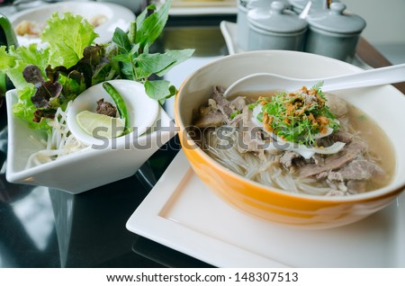Pho Lao style noodle soup with vegetables on table - stock photo