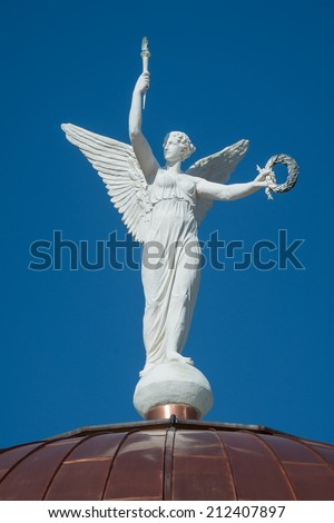"PHOENIX, ARIZONA - AUGUST 6: ""Winged Victory"" statue (actually a wind vane) on the dome of the Arizona State Capitol building on August 6, 2014 in Phoenix, Arizona - stock photo"