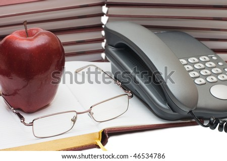 Phone, apple and glasses on the book - stock photo